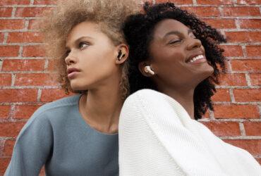 Two women wearing House of Marley Rebel true wireless earbuds